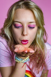 Portrait of rouged young woman blowing glimmer in front of pink background - MGIF00110