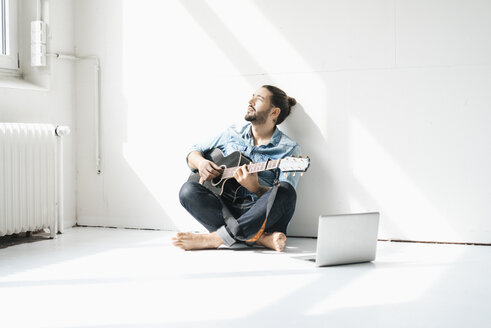 Man sitting with laptop on floor in a loft playing guitar - JOSF01527
