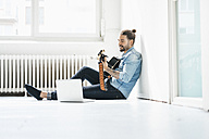 Man sitting with laptop on floor playing guitar - JOSF01530
