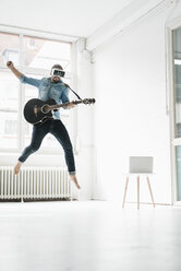 Man with guitar wearing Virtual Reality Glasses jumping in the air in a loft - JOSF01533