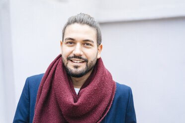 Portrait of smiling businessman wearing scarf - JOSF01539