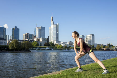 Germany, Frankfurt, young woman stretching at riverside - PUF00699