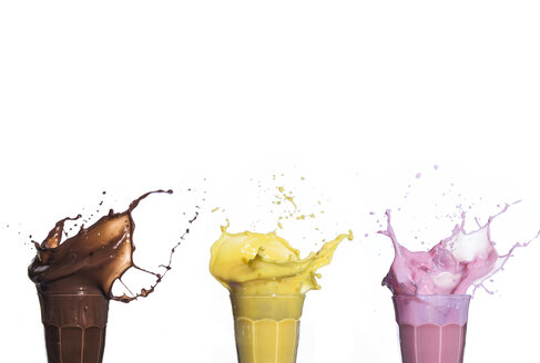 Shakes of different flavors exploding on white background - ABZF02172