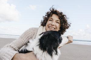 Happy woman with dog on the beach - KNSF02539