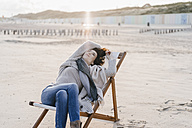 Woman sitting on deckchair on the beach - KNSF02542