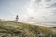 Woman practicing yoga in beach dune - KNSF02545