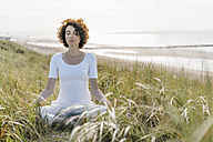 Woman practicing yoga in beach dune - KNSF02548