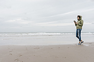 Woman walking on the beach with tablet - KNSF02554