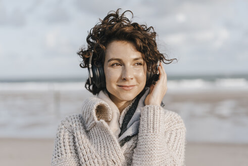 Smiling woman on the beach with headphones - KNSF02557