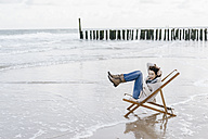 Woman sitting on deckchair on the beach raising her legs - KNSF02572