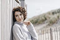 Portrait of woman leaning against beach hut - KNSF02575