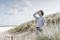 Woman standing in beach dune - KNSF02578
