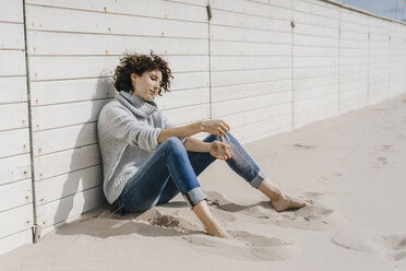 Woman sitting on the beach leaning against wooden wall - KNSF02581