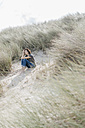 Woman sitting in beach dune - KNSF02590