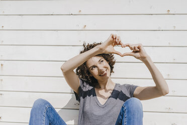 Woman leaning against wooden wall shaping heart with her hands - KNSF02593