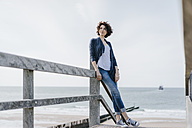 Woman standing on boardwalk at the beach - KNSF02599