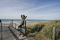 Woman standing on boardwalk at the beach - KNSF02602