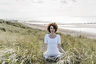 Woman practicing yoga in beach dune - KNSF02614