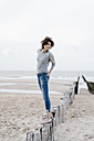 Woman standing on wooden stake on the beach - KNSF02620