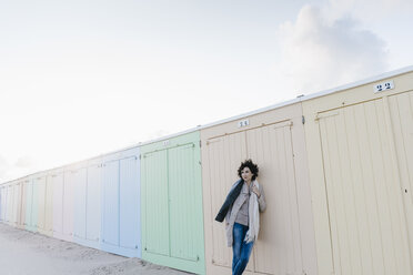 Woman leaning against beach hut - KNSF02626