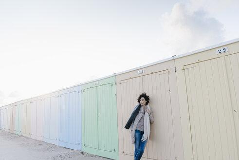 Woman leaning against beach hut - KNSF02626