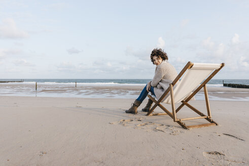 Woman sitting on deckchair on the beach - KNSF02632