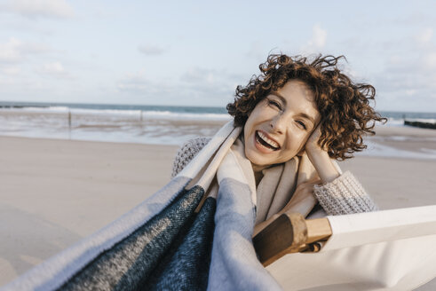 Portrait of happy woman in deckchair on the beach - KNSF02635