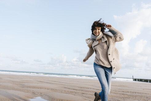 Happy woman running on the beach - KNSF02644