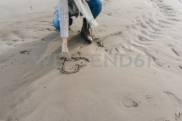 Woman crouching on the beach drawing a heart in the sand - KNSF02647