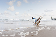 Woman sitting on deckchair on the beach - KNSF02653