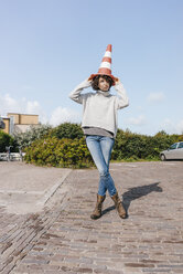 Playful woman with traffic cone - KNSF02659