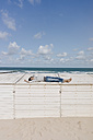 Woman lying on wooden box on the beach - KNSF02668