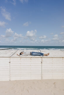Woman lying on wooden box on the beach - KNSF02668