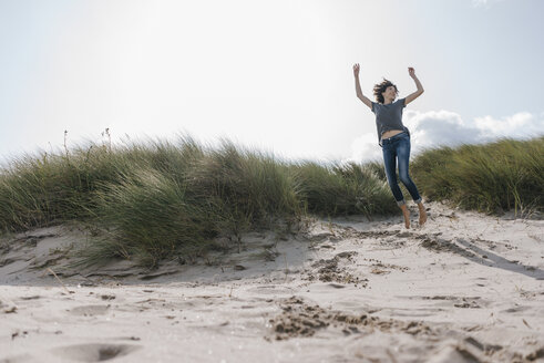 Happy woman jumping in beach dune - KNSF02671