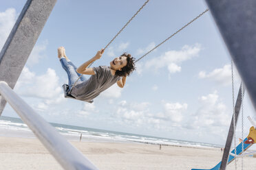 Happy woman on a swing on the beach - KNSF02674