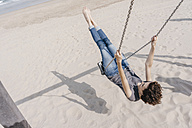 Happy woman on a swing on the beach - KNSF02677