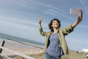Happy woman at the beach taking a selfie - KNSF02689