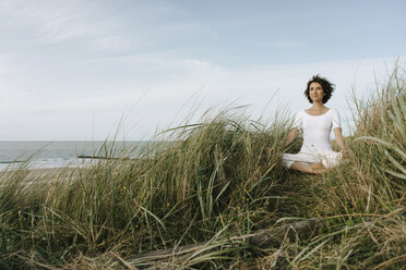 Woman practicing yoga in beach dune - KNSF02695