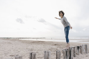 Happy woman balancing on wooden stake on the beach - KNSF02698