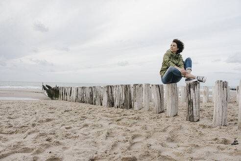 Woman sitting on wooden stake on the beach - KNSF02704