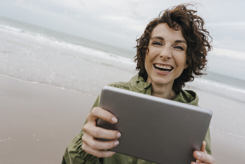 Portrait of happy woman with tablet on the beach - KNSF02707