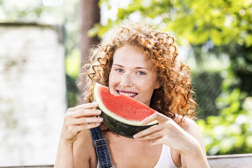 Portrait of redheaded young woman with watermelon - FMKF04423