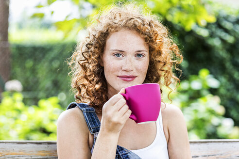 Portrait of redheaded young woman with pink coffee cup - FMKF04426
