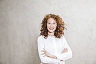 Portrait of laughing redheaded young woman with arms crossed - FMKF04429