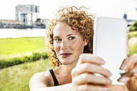 Germany, Cologne, portrait of freckled young woman taking selfie with cell phone - FMKF04432