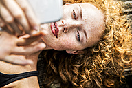 Portrait of redheaded young woman lying on bench using cell phone - FMKF04435