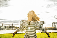 Germany, Cologne, young woman enjoying sunlight - FMKF04438