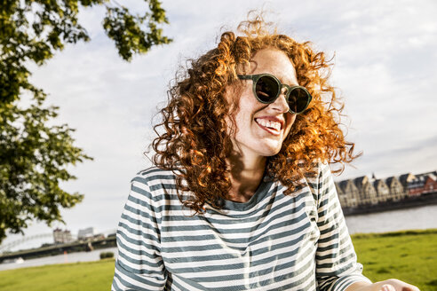 Germany, Cologne, portrait of laughing redheaded young woman wearing sunglasses - FMKF04441