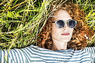 Portrait of young woman relaxing on a meadow wearing sunglasses - FMKF04444