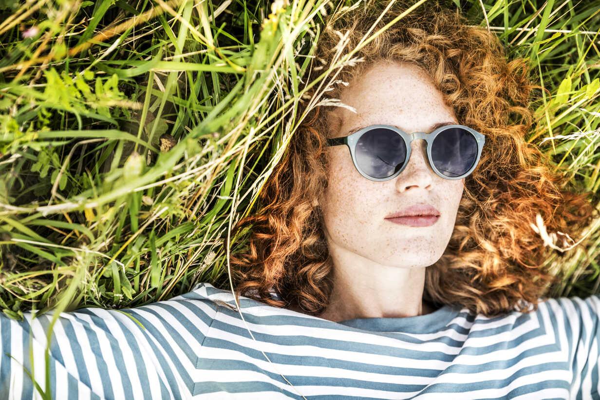 Portrait of young woman relaxing on a meadow wearing sunglasses - FMKF04444 - Jo Kirchherr/Westend61